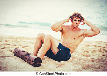 Man Doing Sit-Ups Outdoors on the Beach - Attractive male...