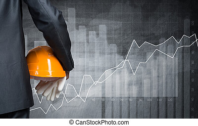 Making a plan - Close up of businessman with helmet in hand...