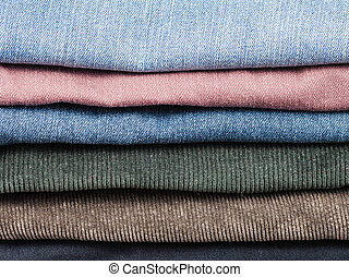 stack of various jeans and corduroy slacks close up