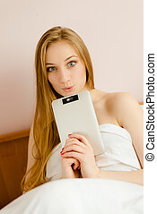 Young surprized blonde female with her tablet pc in bed -...
