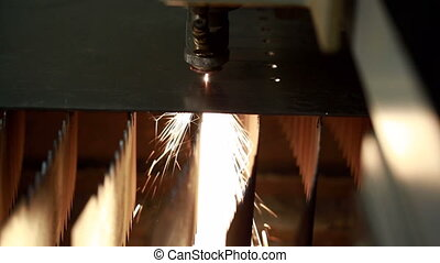 View of modern machine makes hole in metal sheet by laser...