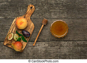 Ripe fruits of peach, plums and pear with honey in a tray....