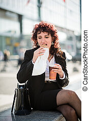 Quick lunch - business woman eating in street - Senior...