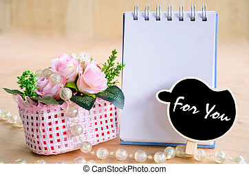 For you wording in black tag and open blank diary with flowers.