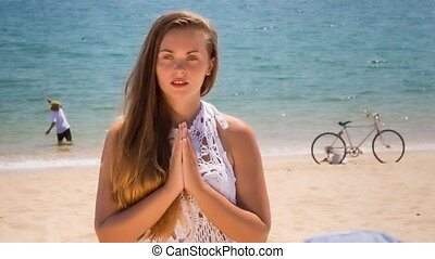 blonde girl in lace meditates in yoga asana on beach -...