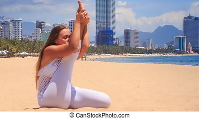 blonde girl in lace shows yoga asana stretching leg - blonde...