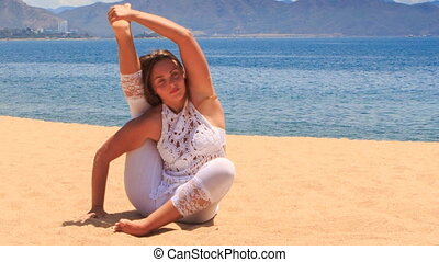 girl in white lace costume shows yoga asana leg behind head...