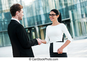 Welcome on board! Two smiling young business people shaking hands while standing outdoors