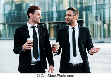 Colleagues and friends. Two cheerful businessmen holding cups on coffee and talking to each other while walking outdoors