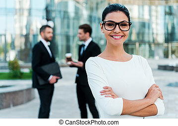 Confident businesswoman. Smiling young businesswoman keeping arms crossed and looking at camera while two her male colleagues talking to each other in the background