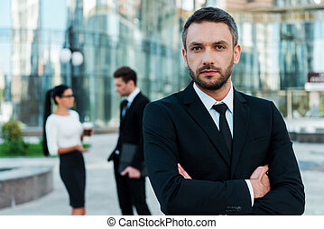 He is great team leader. Confident young businessman keeping...