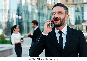 Always in touch with his clients. Cheerful young businessman talking on the phone and looking away while two his colleagues talking to each other in the background