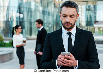 Business texting. Serious young businessman holding mobile phone and looking at it while two his colleagues talking to each other in the background