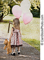 Child Carrying Balloons and Dragging a Teddy Bear - Photo...