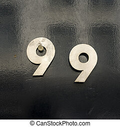 Number 99 - metal number ninety nine, nailed to a lacquered...