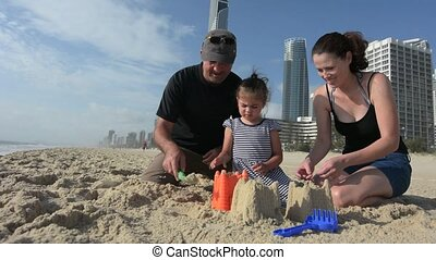 Young family builds sand castle in Surfers Paradise...