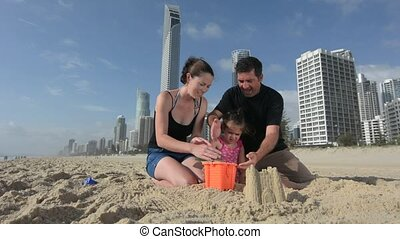 Family builds sand castle 01 - Family builds sand castle on...
