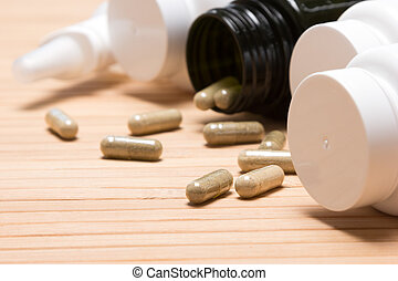 Scattered capsules with plastic jars - Close-up of...