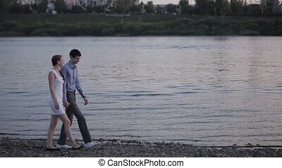 couple walking at sunset along the river - he guy and the...