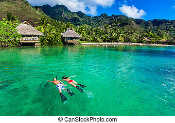 Young couple snorkeling over reef next to resort on a...
