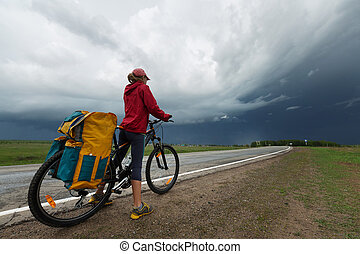 Hiker with bicycle standing on the paved road with storm...