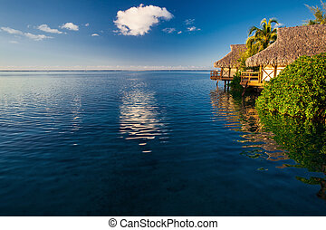 Villas in a tropical resort and blue sky reflected in the blue ocean