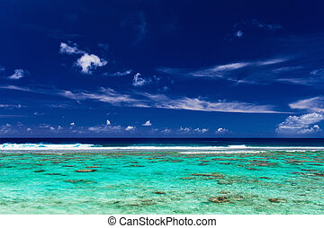 Blue sky and surf beach on a coral reef, tropical island