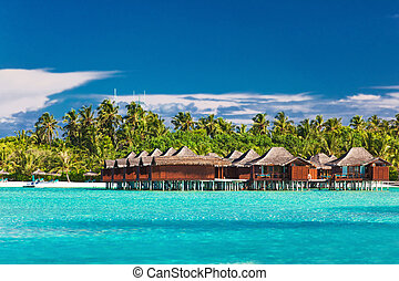Overwater bungallows in lagoon on tropical island with coconut palm trees