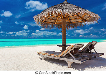 Two chairs and umbrella on a tropical beach with amazing lagoon