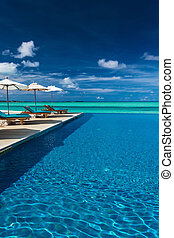 Infinity swimming pool on the beach of tropical island with...