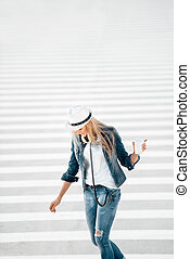 Walking on zebra cross. - Beautiful young woman in a hat and...