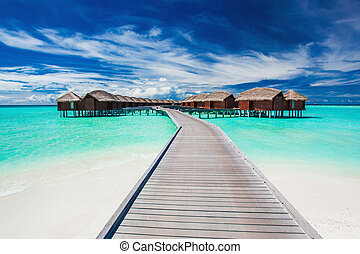 Overwater villas on the tropical lagoon connected by jetty -...