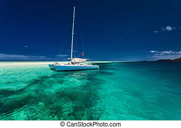 White catamaran in shallow tropical water with snorkeling...