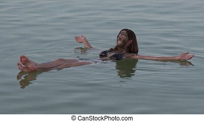 Young Woman floating on the Dead Sea, Israel - Young woman...