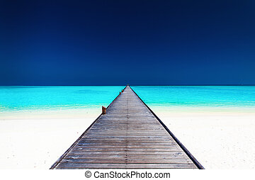 Wooden long jetty over lagoon with amazing clean water