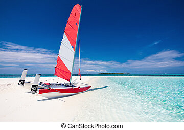 Sailing boat with red sail on a beach of deserted tropical island with blue water