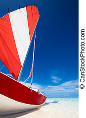 Sailing boat with red sail on a beach of deserted tropical island