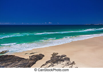 Tropical beach with surf waves on Gold Coast, Australia