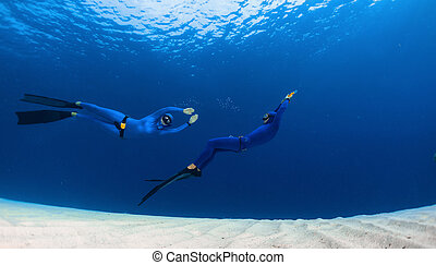 Freedivers - Two freedivers having fun over the sandy sea...