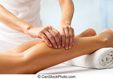 Detail of hands massaging human calf muscleTherapist...