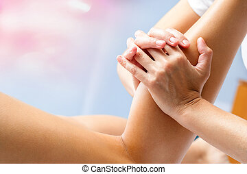 Female hands massaging calf muscle. - Macro close up of...