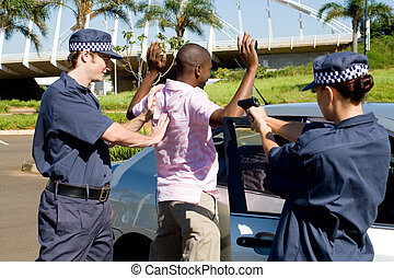 arrested - armed police officers arresting a young criminal