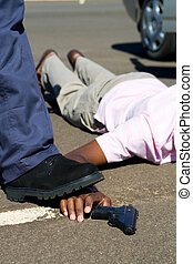criminal - an arrested criminal laying on the floor with...