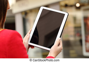 Woman using and showing a blank tablet screen
