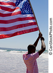 flag - a tall man holding the american flag up high on beach