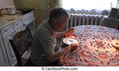 woman eats soup at the table - The elderly woman eats soup...