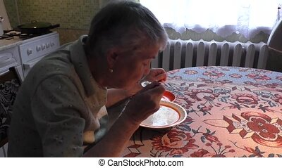 woman eats soup at the table