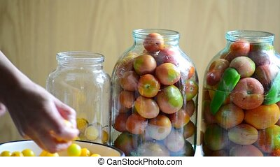 Woman lays tomatoes and cucumbers in jars Home canning for...