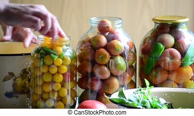 Woman lays tomatoes and cucumbers in jars. Home canning for...