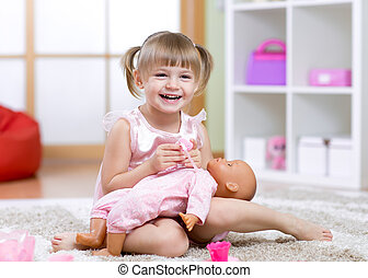 Kid girl plays with doll at home in the children room
